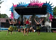 Five female dancers wave their hands in the air as they perform on the grass in front of the main stage. They wear brightly patterned skirts and headscarves made of batik fabric and are accompanied by male drummers.