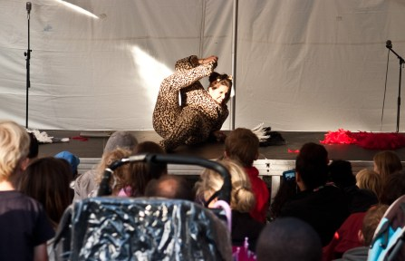 A female contortionist grimaces as she holds her leg behind her head, lying down on the stage. She is wearing a leopard-print onesie and holding a fan made of feathers