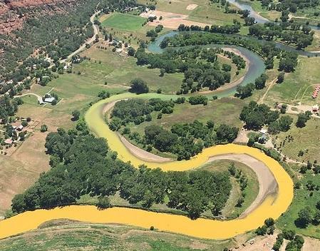 toxic sludge flows down the Animas river in Colorado