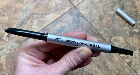 A hand holding an eyebrow pencil
