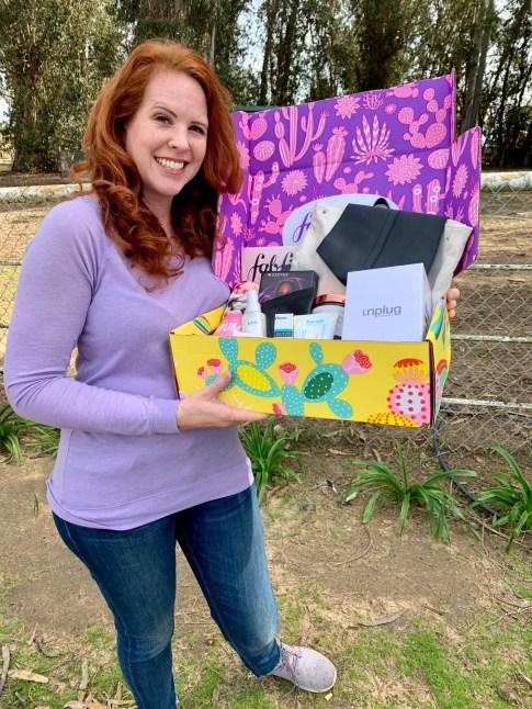 A woman holding a FabFitFun subscription box