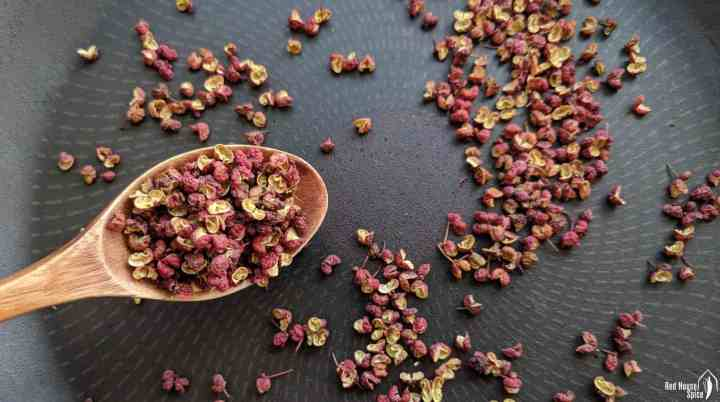 Whole Sichuan peppercorns in a frying pan
