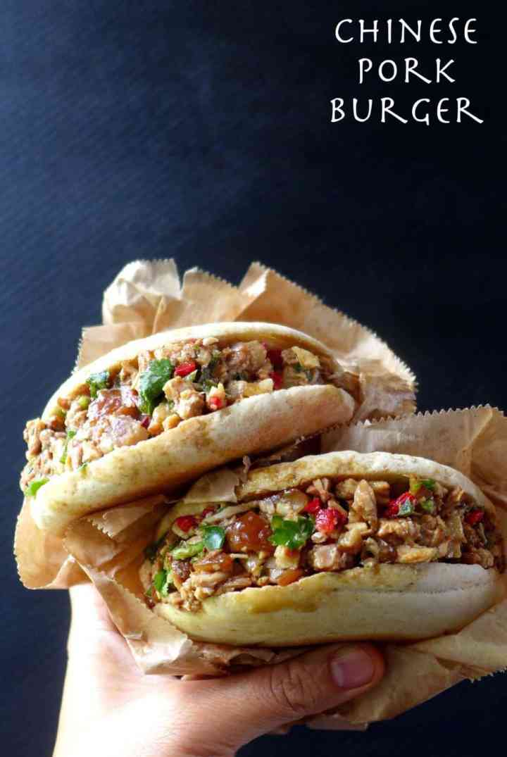 Two Chinese pork burgers (Rou Jia Mo) wrapped in paper.