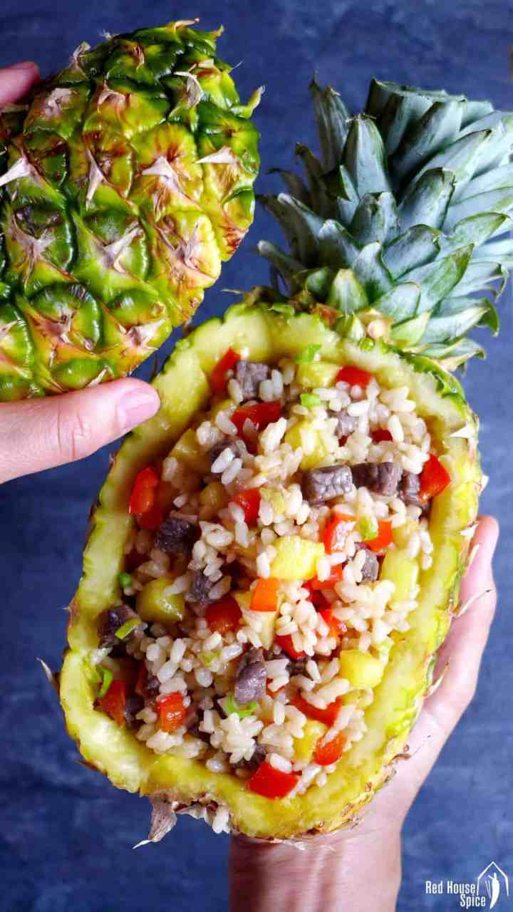 A hollowed pineapple with fried rice inside