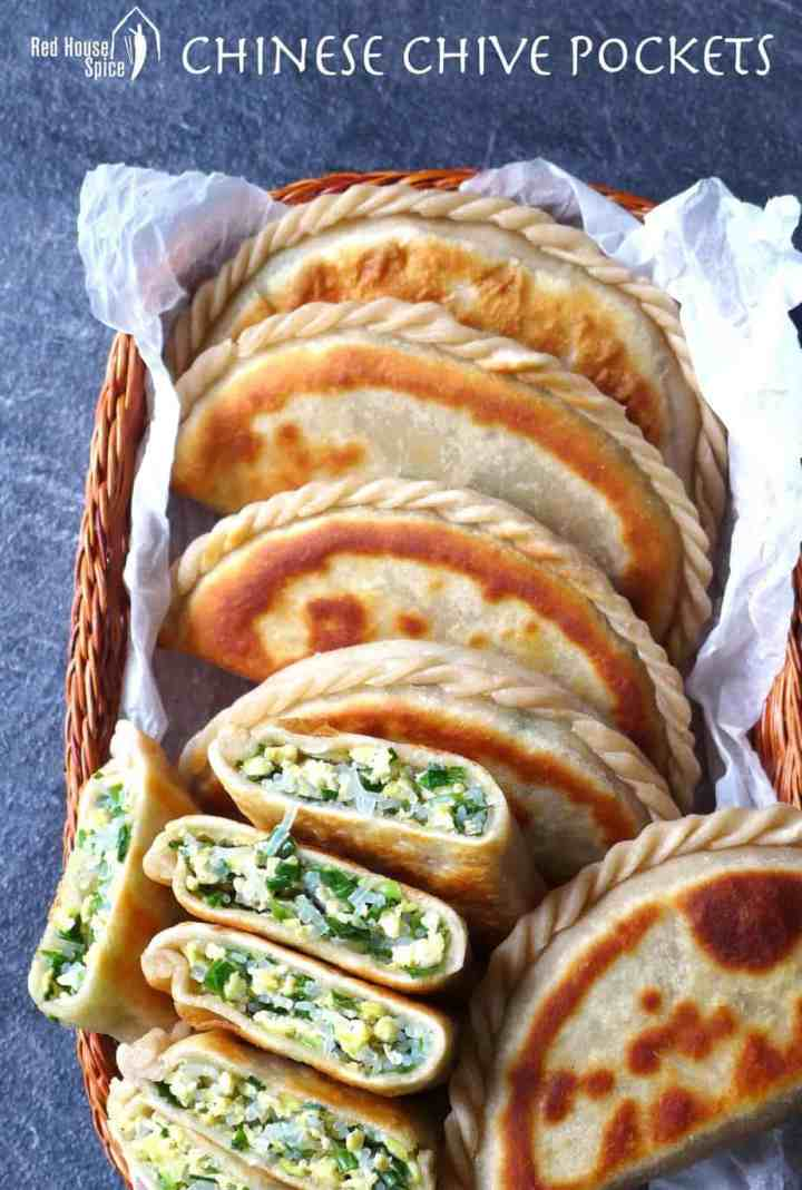 Chinese chive pockets in a basket. Some are cut in halves. You can see the chive and egg filling.