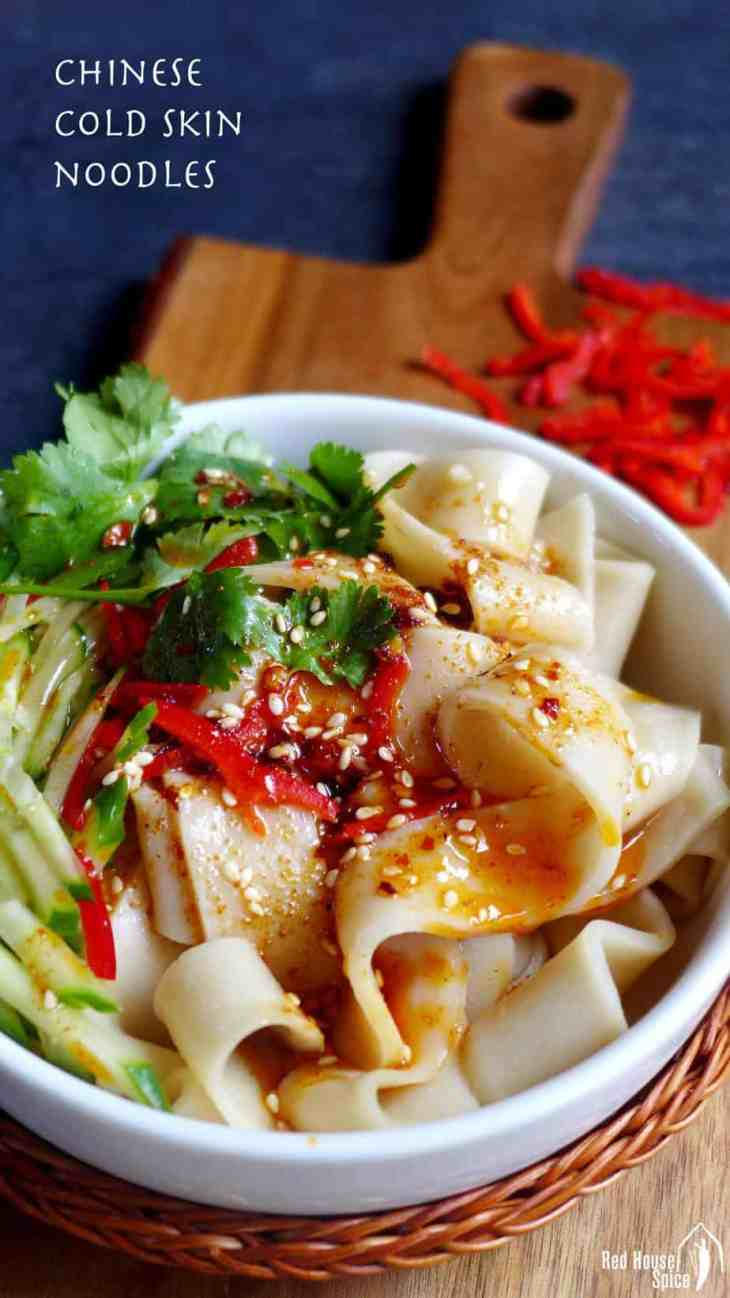 Liang Pi (cold skin noodles) seasoned with sauce and chilli oil, and garnished with cucumber, fresh chilli and coriander.