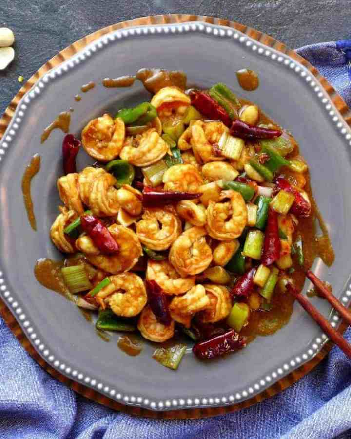 A picture from above of a plate of Kung Pao shrimp with a pair of chopsticks at the side.