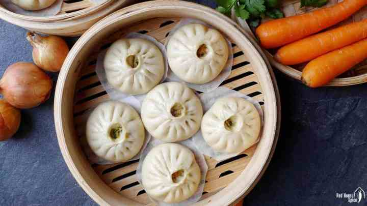 Six steamed bao buns in a bamboo steamer
