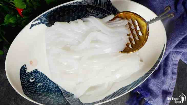 Use a special slicer to make noodle like stripes from a block of Mung bean jelly (Liangfen).