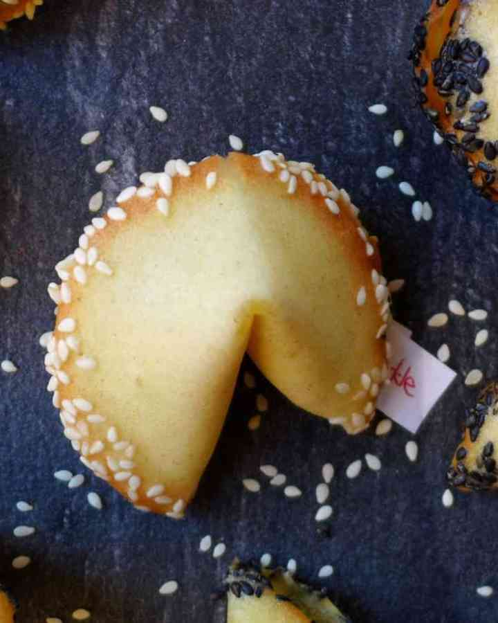 Homemade fortune cookies rimmed with white and black sesame seeds.