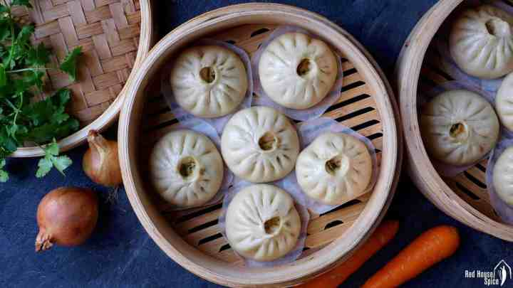 Freshly steamed bao buns in a bamboo steamer.