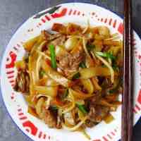 a plate of stir fried rice noodles with beef
