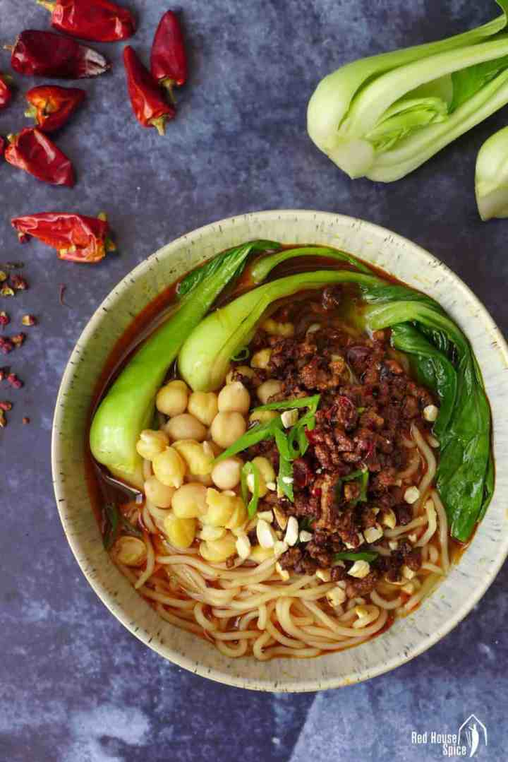 A bowl of Chongqing noodles topped with minced meat and chickpeas.