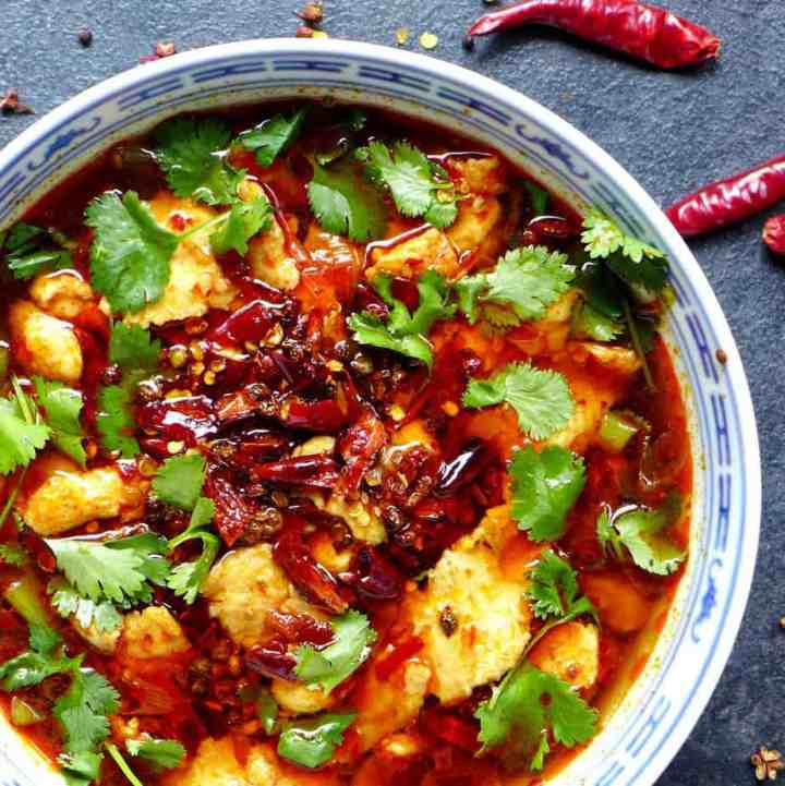 A bowl of Sichuan boiled fish garnished with chillis and coriander.