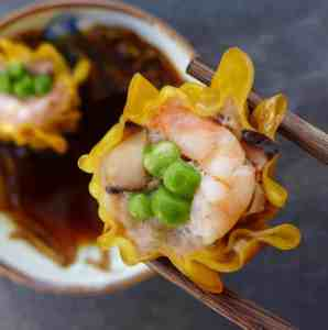 A shrimp & pork shumai held by a pair of chopsticks