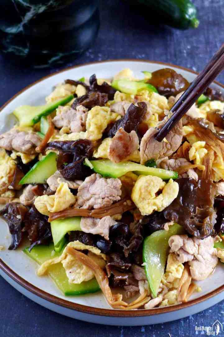 Chopsticks picking up a piece of pork from a plate of Moo Shu Pork