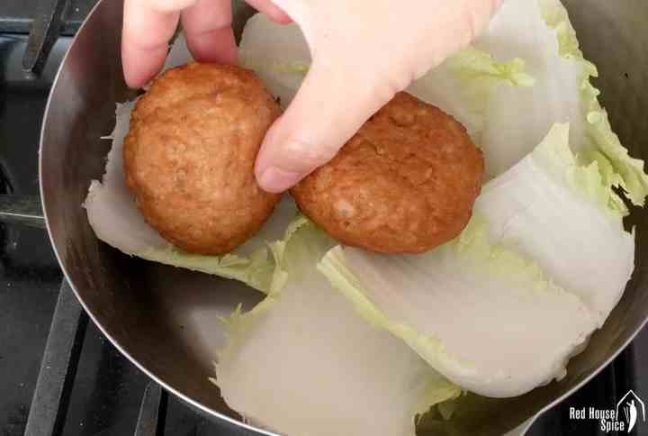 Putting meatballs into a pot over cabbage leaves