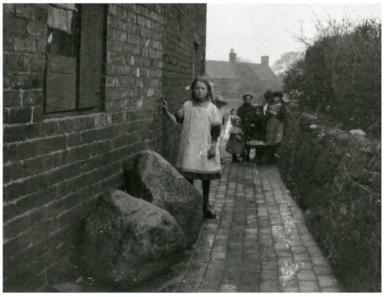 B+W image of Child with 2 anvil stones in Sandbank backyard
