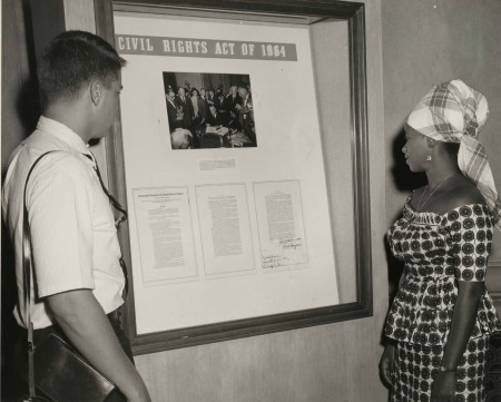 Visit of Mrs. Gladys Sheriff to National Archives, July 23, 1964. Viewing Civil Rights Act of 1964 exhibit, with a visitor. Mrs. Sheriff is assistant librarian of Fourah Bay College, University College, Freetown, Sierra Leone.