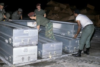 US Military personnel stack transfer cases containing the remains of the victims of the Jonestown Tragedy onto a pallet for shipment to Dover Air Force Base, Delaware (NAID 6413440)