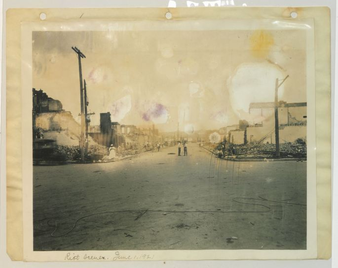 image of a road intersection with burned out/destroyed buildings on both sides