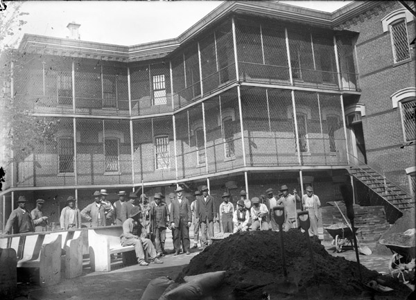 group of Black patients at St Elizabeths standing in a line with shovels and dirt pile in foreground