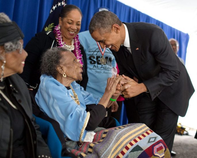 President Obama bending down to greet 103 year old Amelia Boynton, seated in a chair