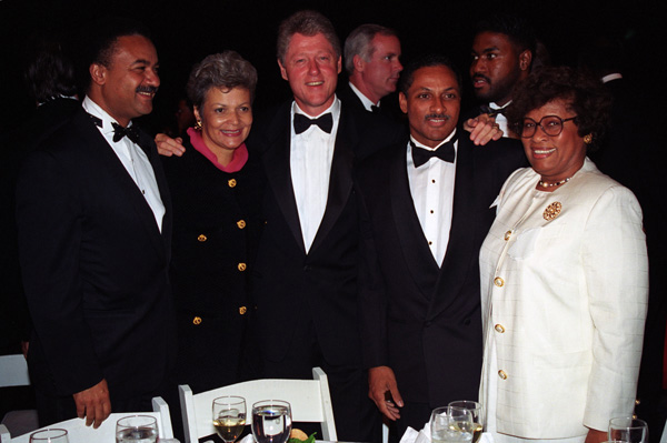 Clinton at the center surrounded by African American members of his cabinet, all standing at a table