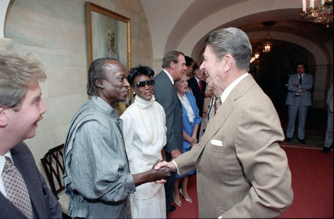 Miles Davis and Cicely Tyson in a receiving line shaking hands with Ronald Reagan