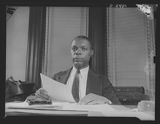 Pickens sitting at desk w/paper in hand