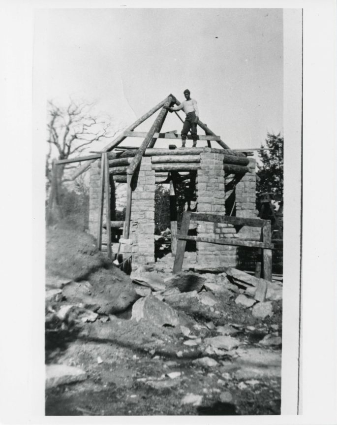 man standing on top of a circular stone structure with the beams for the roof that is about to be completed