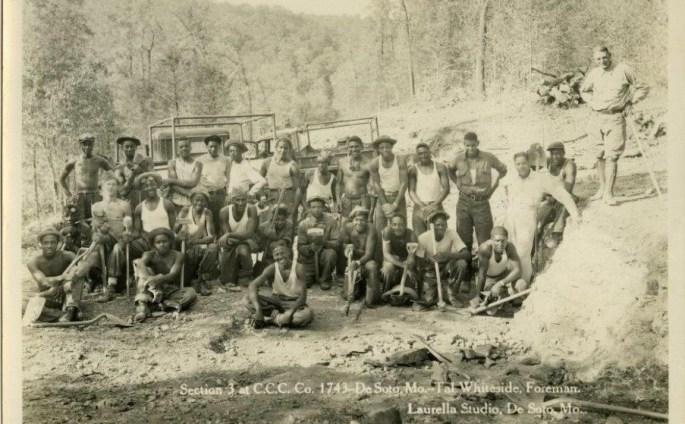 group of men in 2 rows posing w/pick axes