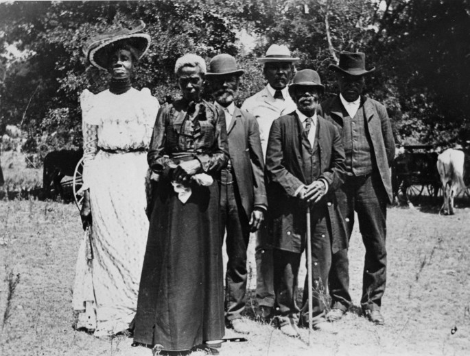 family of 6 adults dressed in suits and dresses posing for photo