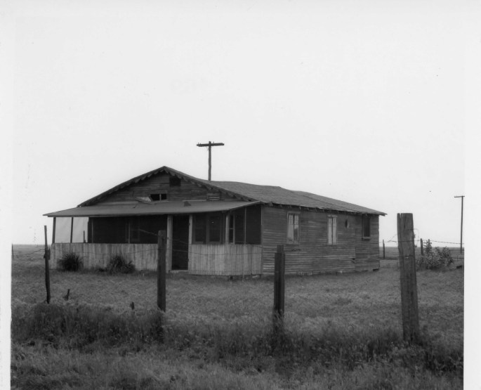 view of wood frame one story house in a field