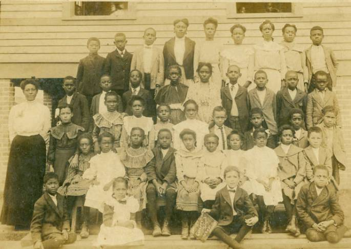 Group photograph of the lower 3rd grade students who are in 5 rows on risers, with teacher  standing off to side