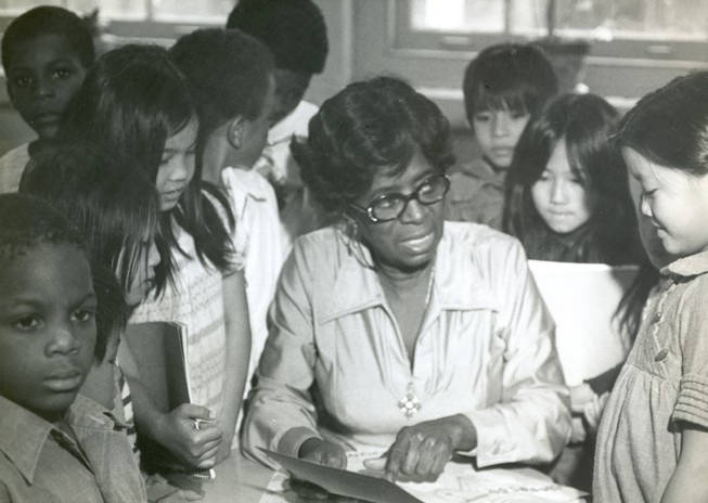 seated teacher pointing at a paper, with students surrounding her