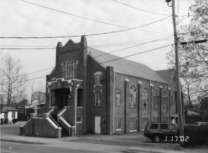 exterior view of church showing front steps and stained glass windows on side
