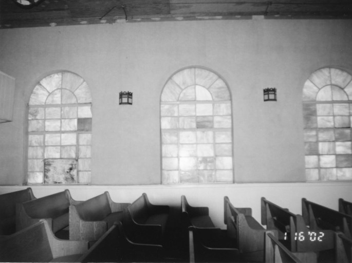 view of interior of church showing wooden pews and stained glass windows