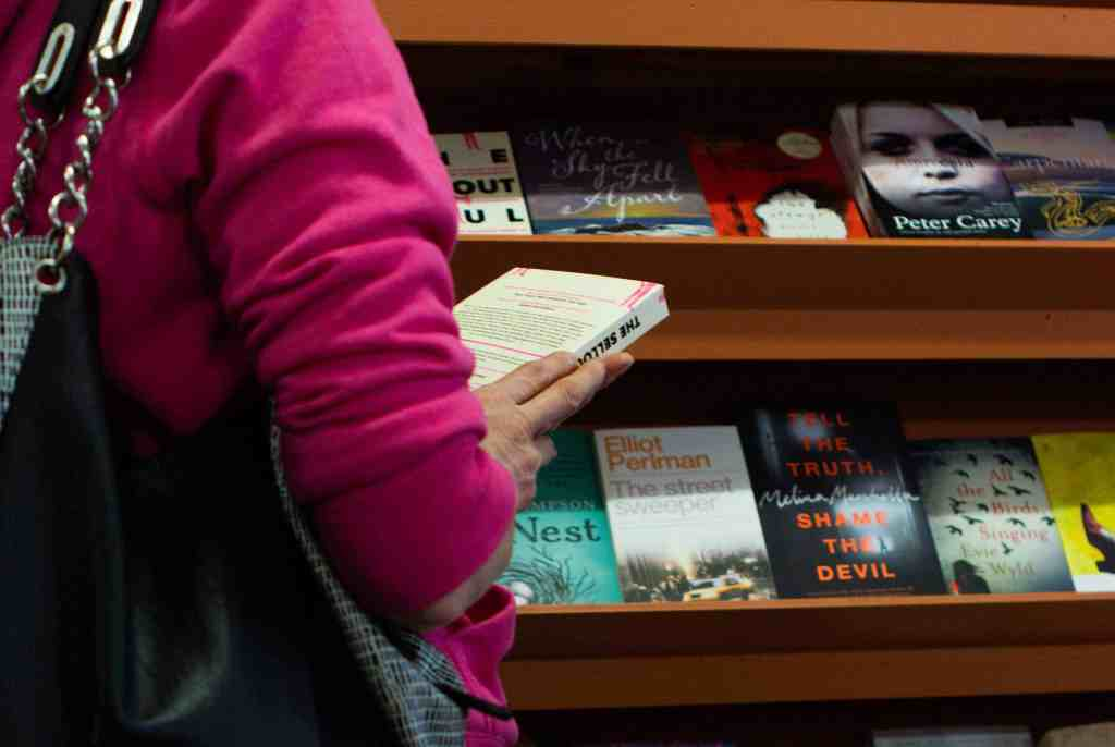 Photo of woman in pink jumper reading a book from the fiction bookshelf at bookstore Red Kangaroo Books