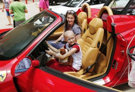 Her mom smiles in the passenger seat as Asa Cook, 13, grips the steering wheel of this shiny red Ferrari Italian sports car. Redline4Kids is a new nonprofit that helps connect kids in the hospital with a chance to see cool cars. Photo by Jim Beckel, The Oklahoman