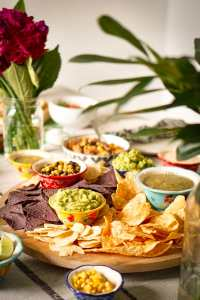 3 or 4 different dips and chips on a serving platter in the center of a table.
