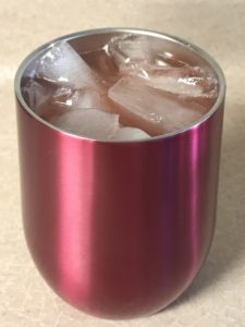 Metal insulated cup with fruity cocktail with ice.