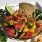 Fresh mango salsa with chip and lime.