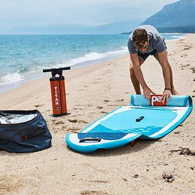 Image of man rolling up inflatable SUP board