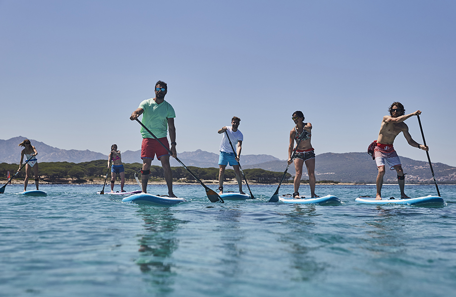 friends paddle boarding together wearing board shorts