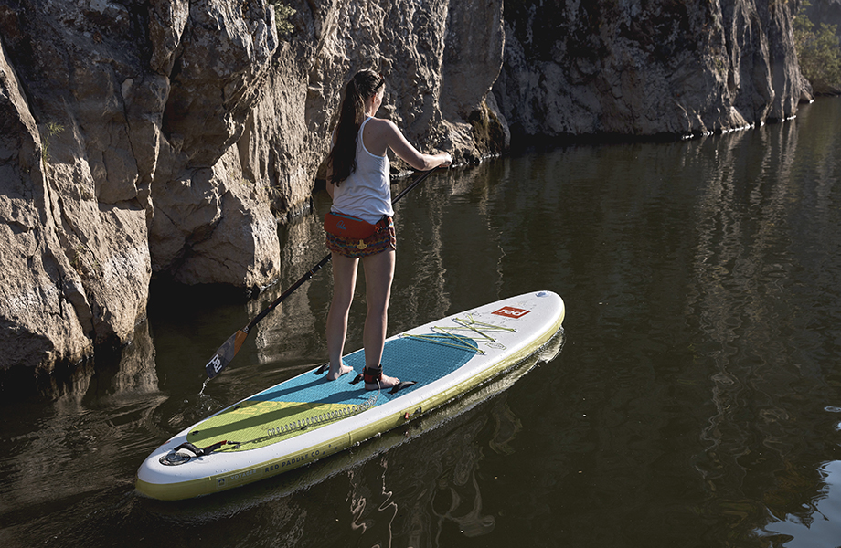 Girl paddles aways wearing shorts and vest top