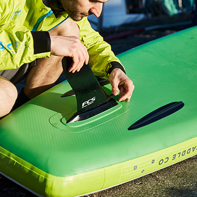 man inserts fin into fin box on paddle board