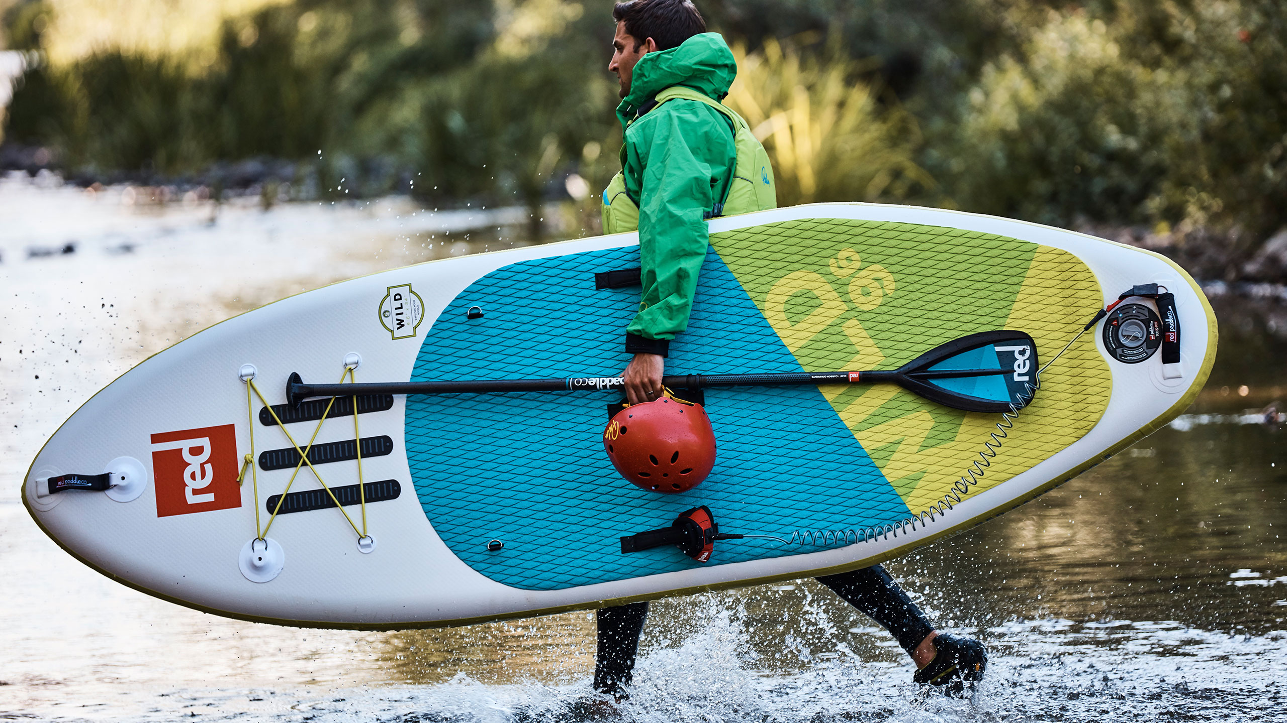 man walks through river carrying his Wild SUP, paddle and helmet
