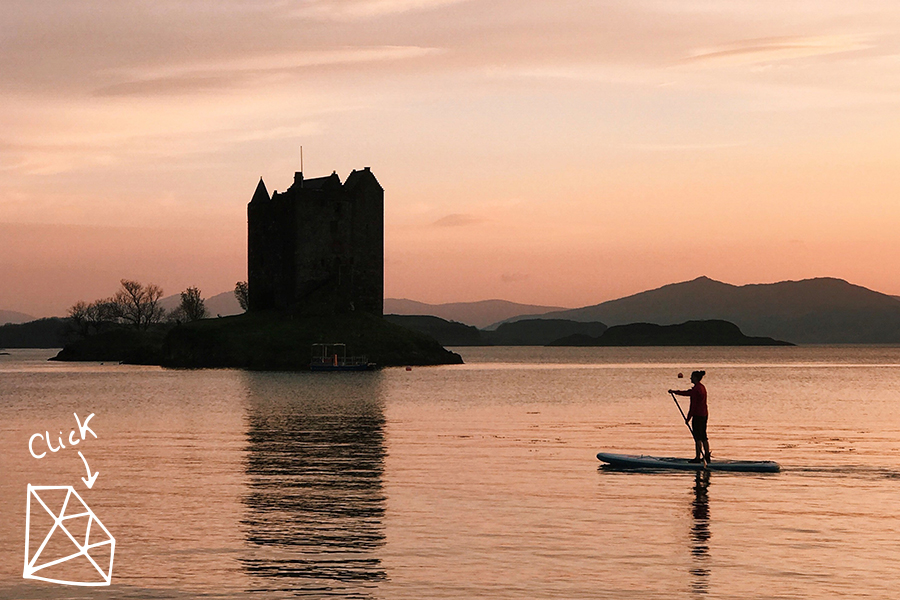 woman paddles past castle at sunset in Scotland