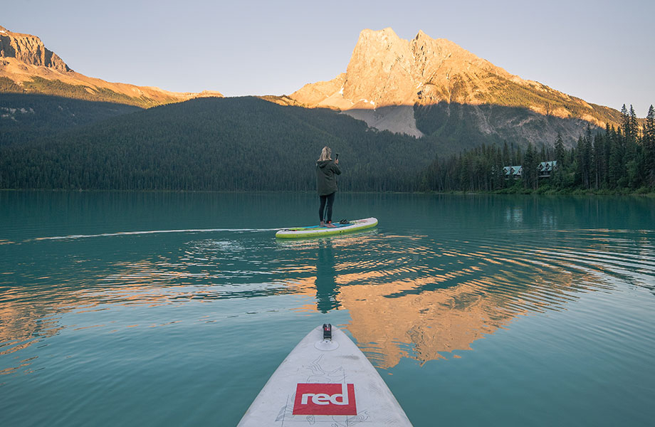 girl paddles with mountains on the horizon